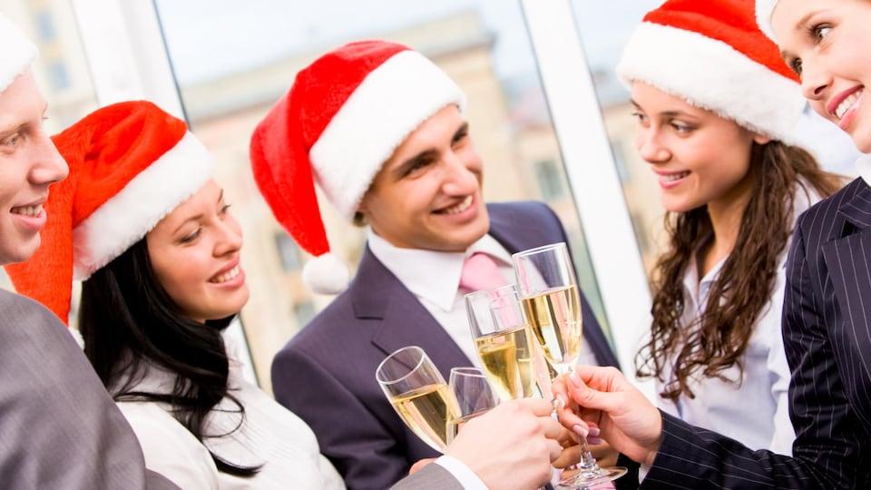 Des collègues de travail festoient pendant leur party de Noël.