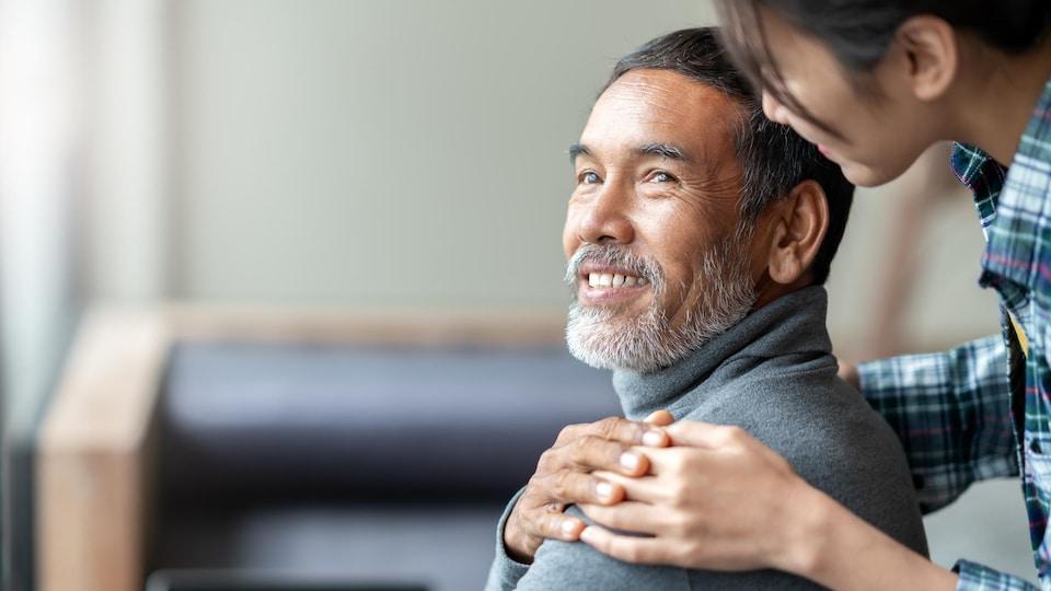 Une personne âgée reçoit la visite d'un membre de sa famille.