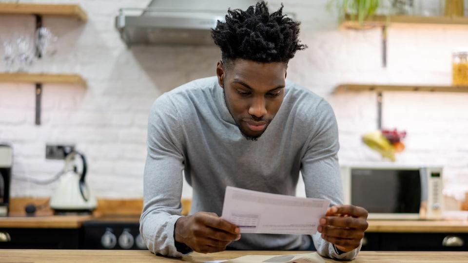 Une personne consulte une facture en papier qu'il vient de recevoir par la poste.