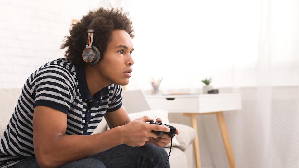 Une personne très concentrée joue à un jeu vidéo.