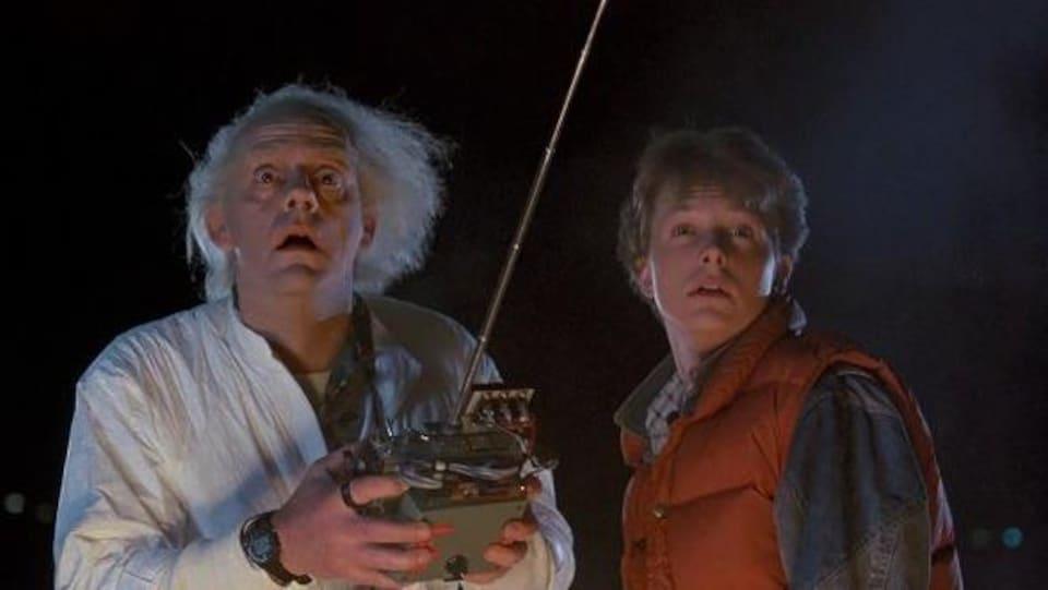 Un homme aux cheveux blancs avec une télécommande, et un autre plus jeune, l'air subjugué.