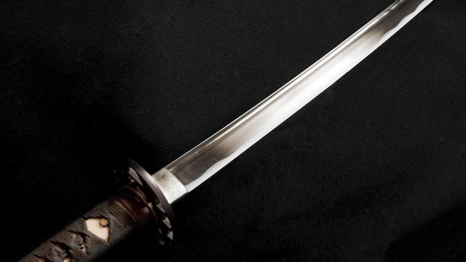Un sabre japonais brille à la lumière.