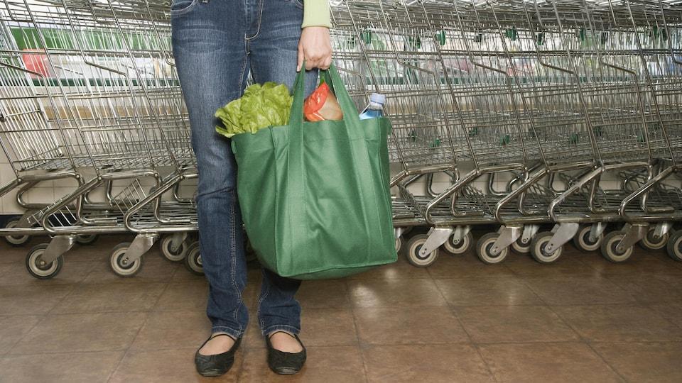Une femme devant des chariots d'épicerie tient un sac réutilisable rempli d'aliments.