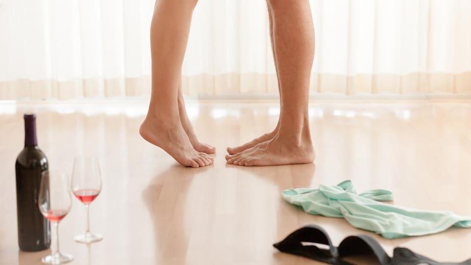Les pieds d'un couple qui se déshabille en prévision d'une relation sexuelle, à côté desquels se trouvent une bouteille de vin, deux coupes et des sous-vêtements.