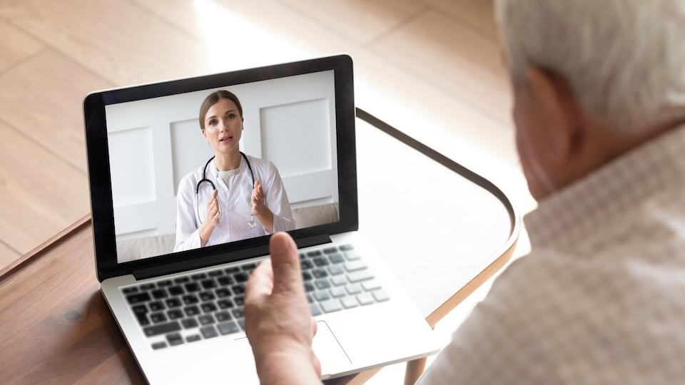 Un homme âgé consulte un médecin sur son ordinateur.