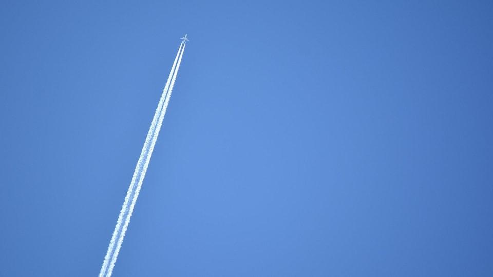 Un avion laisse une traînée de condensation dans le ciel.