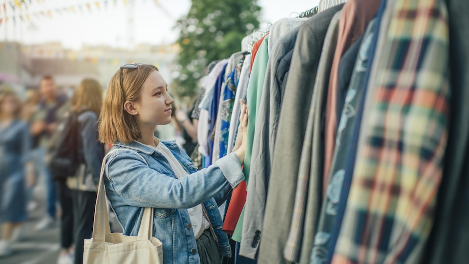 Une jeune femme magasine une pièce de vêtements dans un marché aux puces.