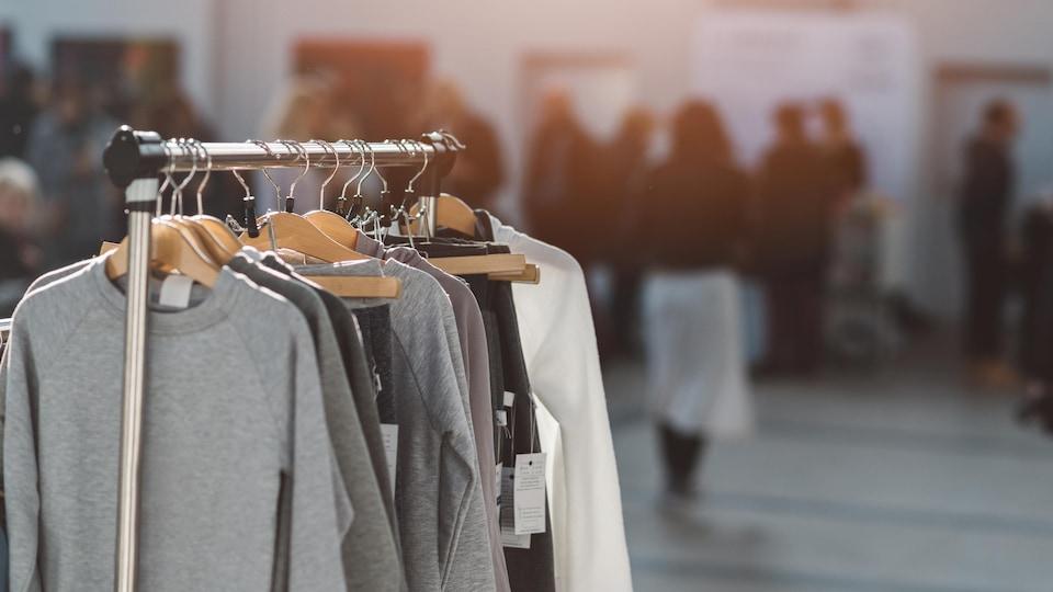 Des vêtements sont accrochés à des cintres dans un magasin.