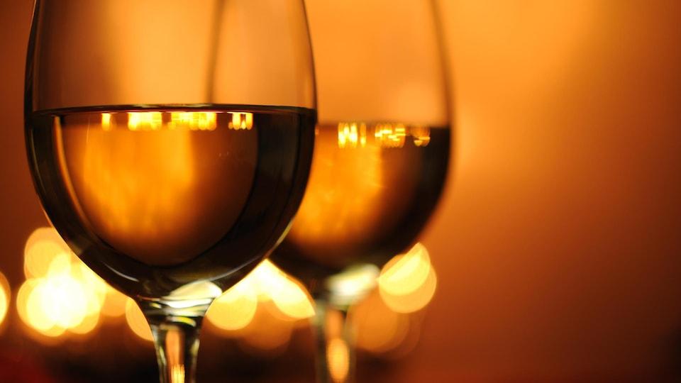 Deux verres de vin orange sont disposés l'un à côté de l'autre.