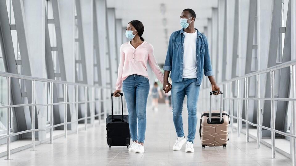 Deux voyageurs portent des masques pendant qu'ils marchent dans un corridor d'aéroport.