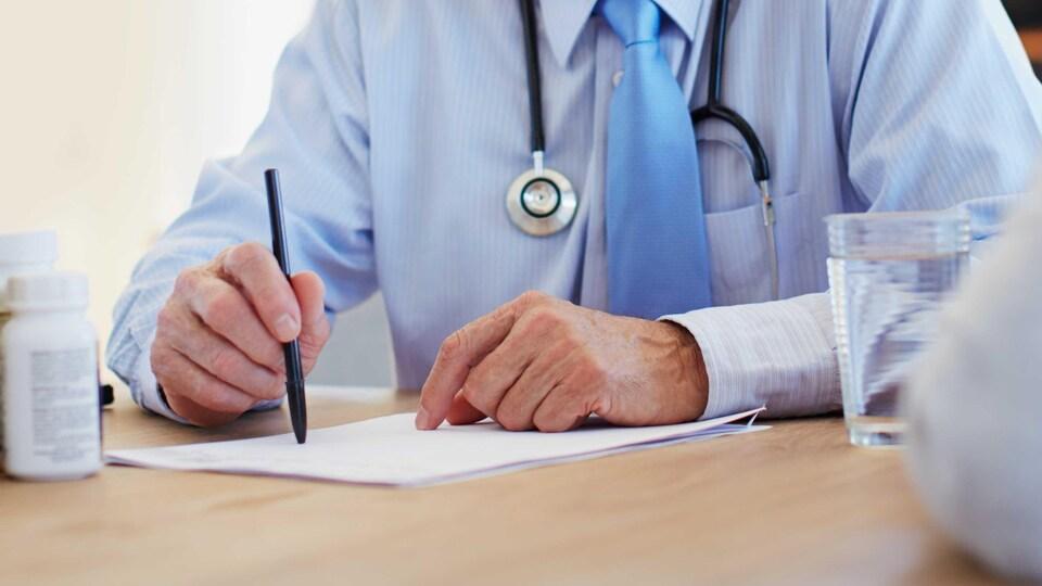 Un médecin d'un certain âge signe un document.