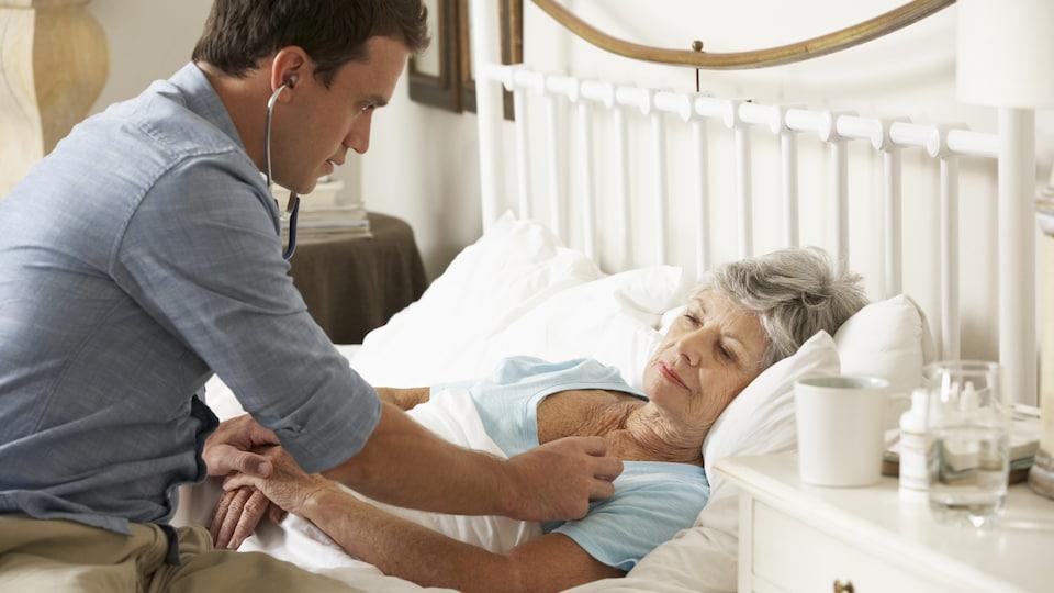 Un médecin pratique des soins à domicile auprès d'une femme âgée couchée dans son lit.