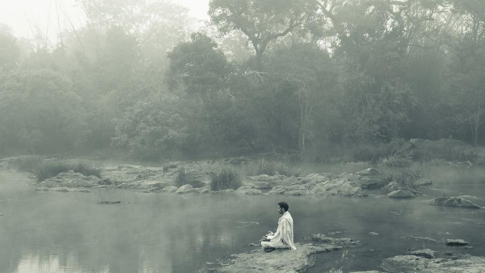 Un homme médite sur le rocher d'une rivière.