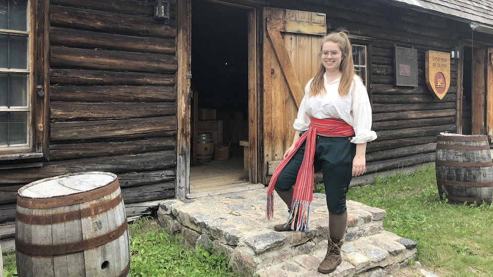 Une femme portant la ceinture fléchée se tient devant un bâtiment d'époque en bois.