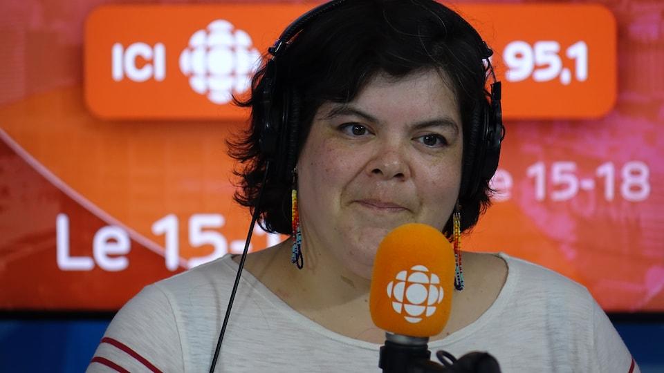 Melissa Mollen Dupuis derrière un micro dans un studio radio de Radio-Canada.