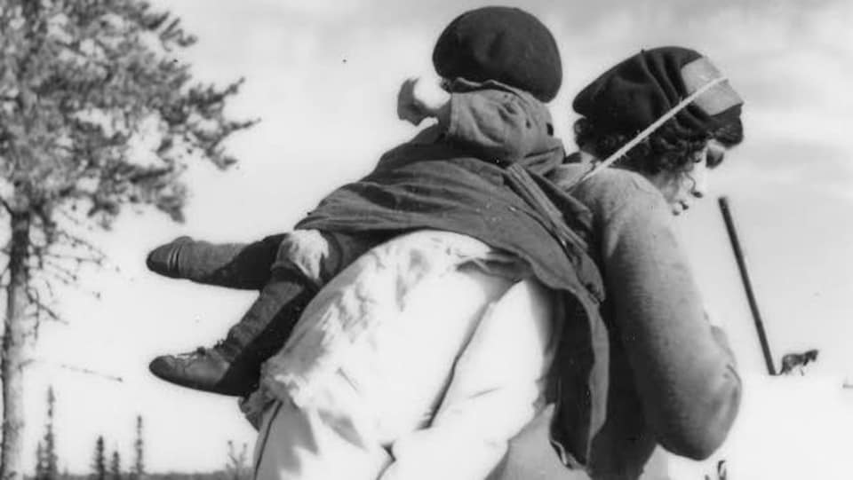 Une femme innue porte un enfant sur son dos, lors d'un portage.