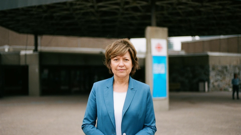 Elle sourit devant la tour de Radio-Canada.