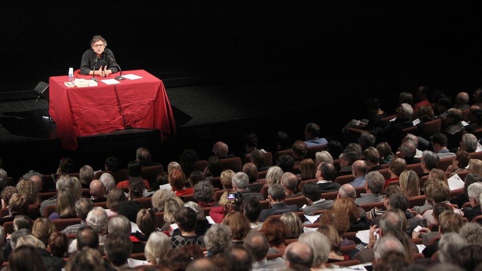 Devant public, il est assis derrière une table avec une nappe rouge.