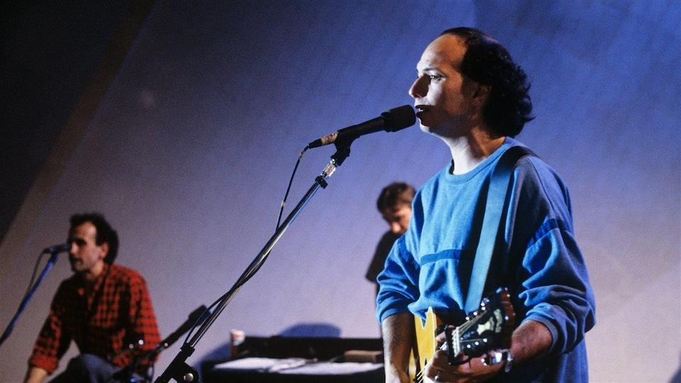 Michel Rivard chante avec deux musiciens.