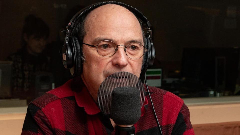 Devant le micro, le musicien est affublé d'une veste à carreaux rouges et noirs.