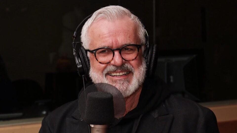 Des écouteurs sur la tête, il est assis derrière un micro en souriant.