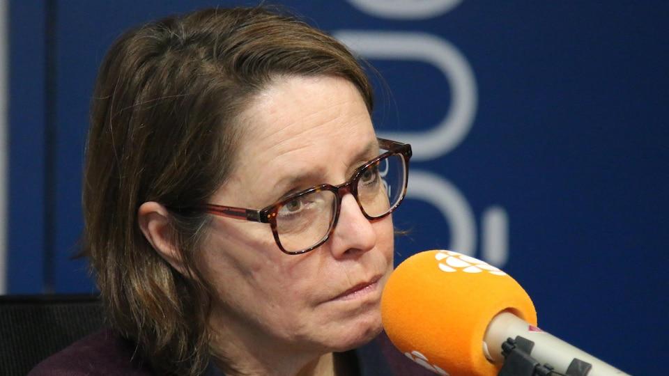 Une femme aux cheveux courts et portant des lunettes de vues parle au micro.