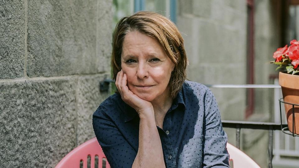 La journaliste pose assise sur un balcon.