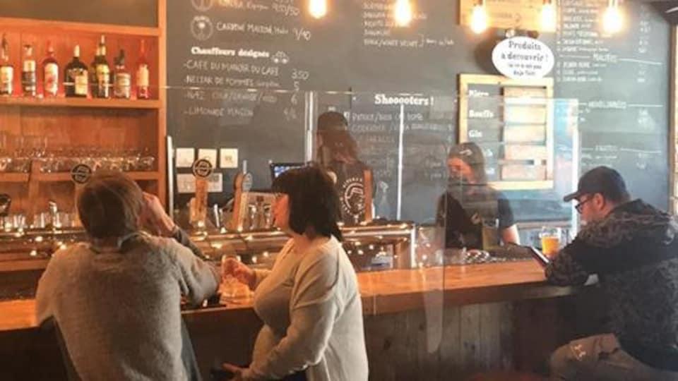 Un bar avec des gens assis au comptoir devant des panneaux de plexiglass