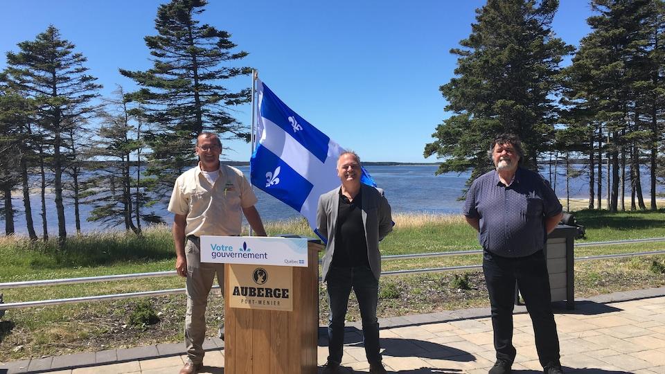 Le ministre Jonatan Julien lors d'une conférence de presse sur l'île d'Anticosti, sur le bord de l'eau entouré de John Pineault, maire et coprésident de Tourisme Côte-Nord et Robin Plante, directeur général Sépaq Anticosti.