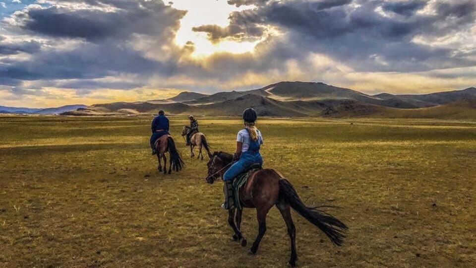 Trois cavaliers dans une plaine, au loin, montagnes surplombées du soleil perçant des nuages. Fabuleux