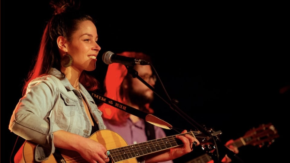 Mireille chante sur scène avec sa guitare. Elle est accompagnée d'un autre guitariste.