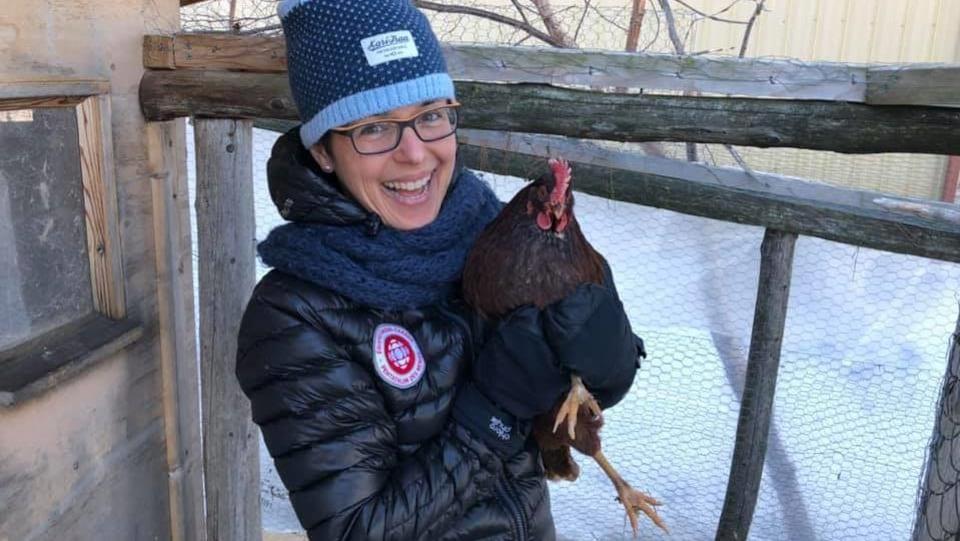 Dans un modeste poulailler, Mireille tient une poule dans ses bras