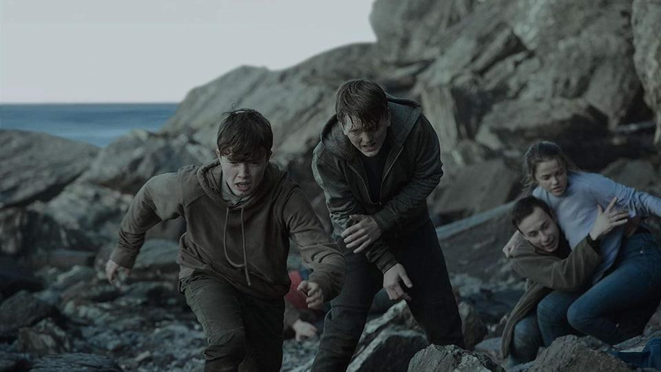 Quatre adolescents courent sur des rochers dans cette image tirée du film <i>Un 22 juillet<i>, de Paul Greengrass.