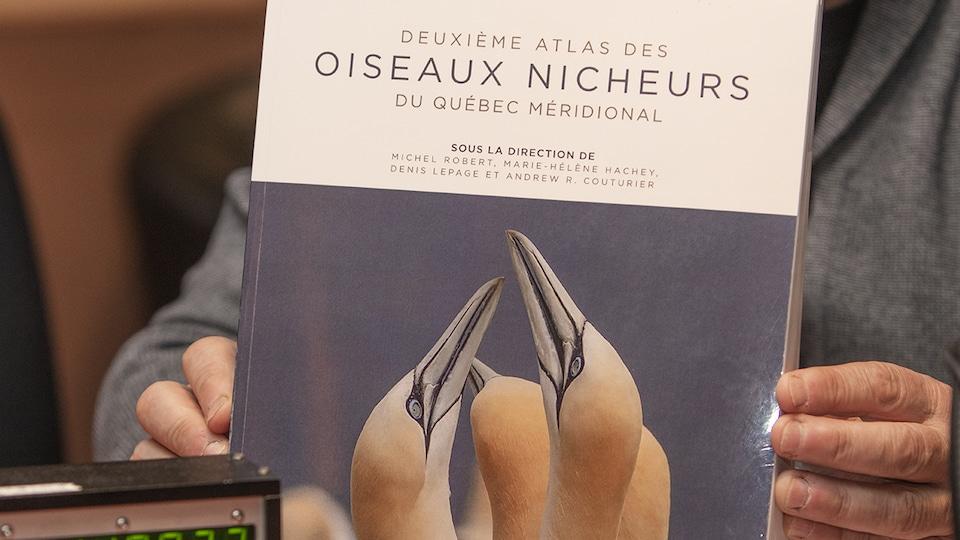 Pierre Gingras tient une copie d'épreuve du <i>Deuxième atlas des oiseaux nicheurs du Québec méridional</i>, à paraître en mars 2019.