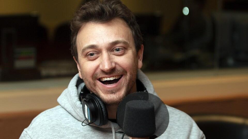 Un homme rit devant un micro dans un studio.