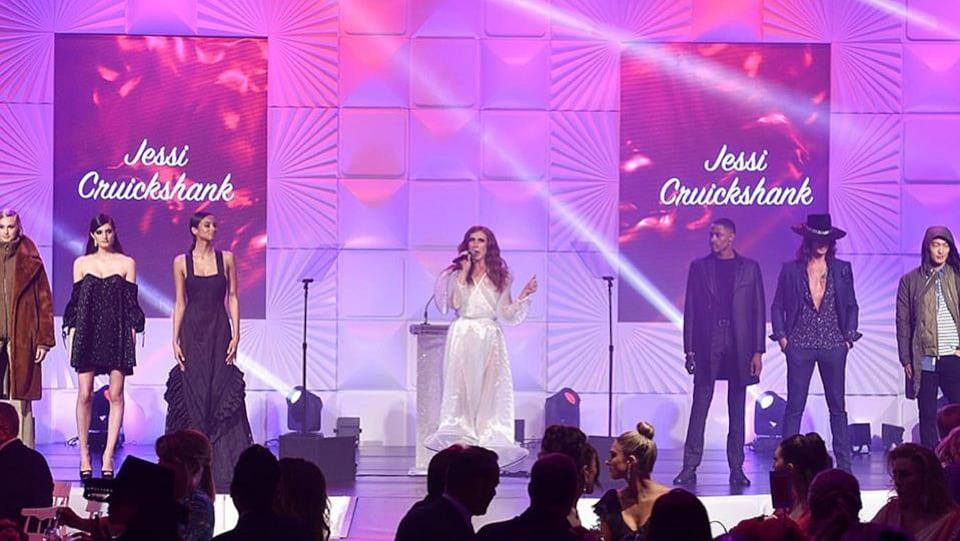 Sur une scène éclairée en rose, une femme en robe blanche parle dans un micro, alors que six autres personnes l'entourent des deux côtés.