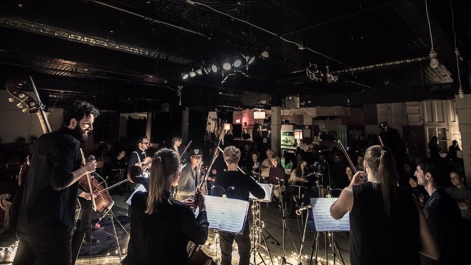 Le groupe collectif9 joue devant un public.