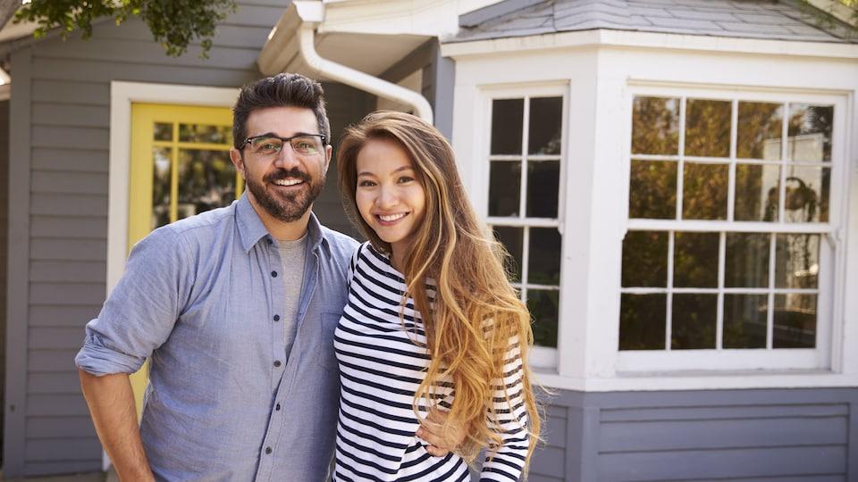 Un homme de race blanche et une femme asiatique se tiennent devant une maison.