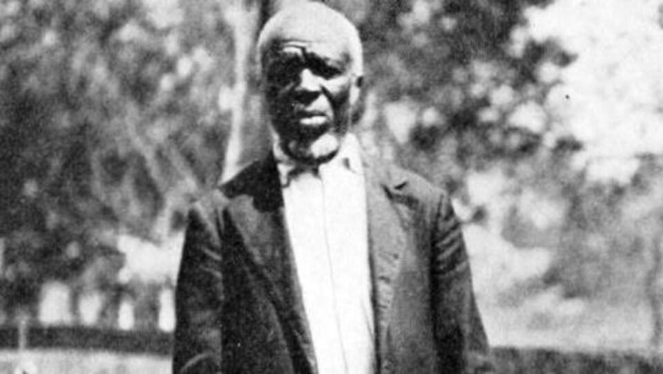Photo en noir et blanc d'un homme en costume qui regarde la caméra.