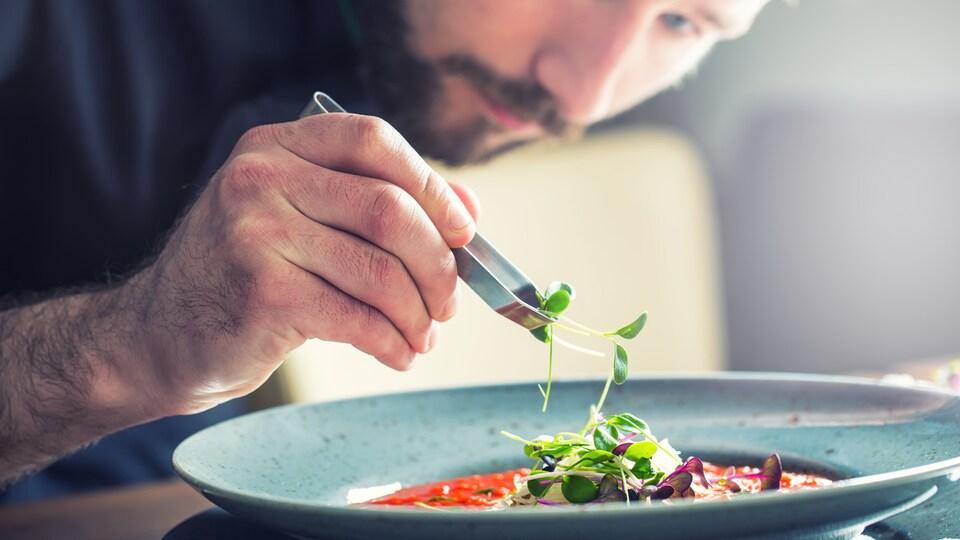 Un chef apporte la dernière touche à une soupe aux tomates particulièrement belle à regarder.