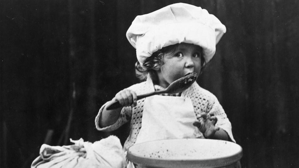 Une petite cuisinière teste la qualité des ingrédients en léchant une cuillère, sur cette photo datant de 1935.