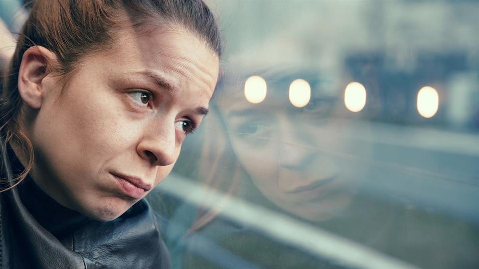 Une femme assise dans un transport en commun regarde par la fenêtre.
