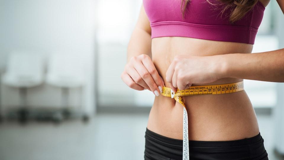 Une femme mesure son tour de taille au moyen d'un ruban à mesurer.