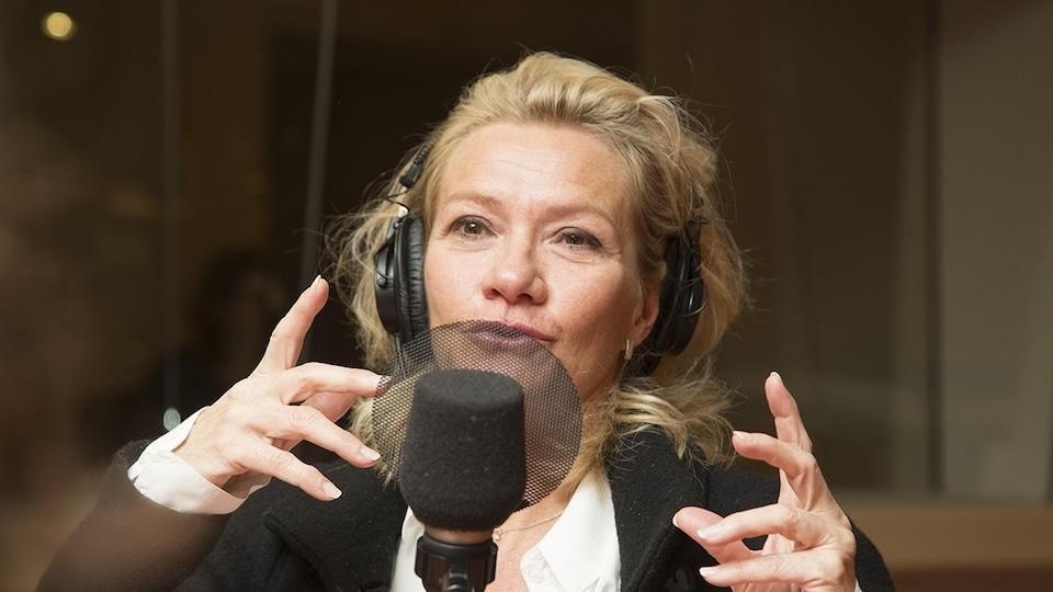 Élise Guilbault devant un micro dans un studio de radio.