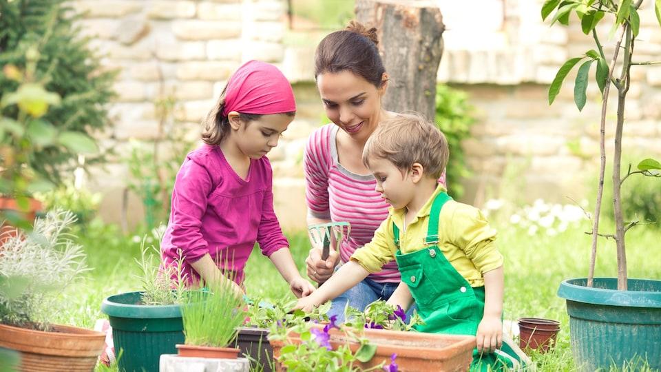Une femme initie ses jeunes enfants au jardinage.