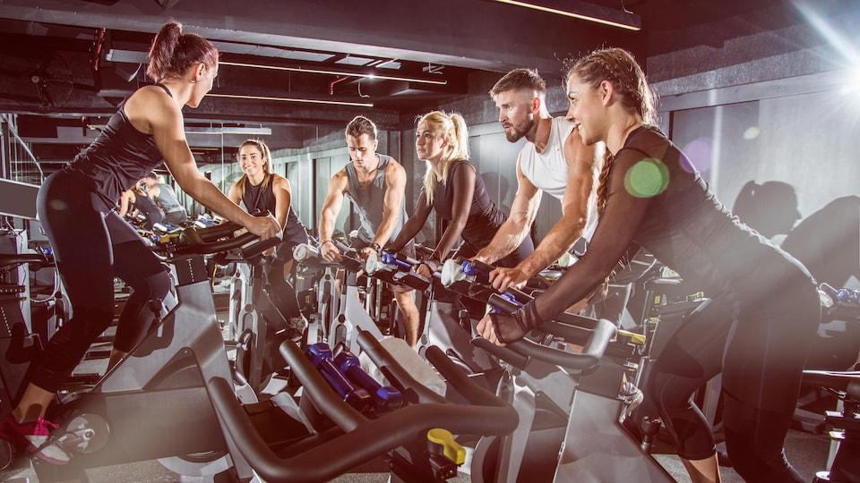 Des hommes et des femmes, jeunes et musclés, font du vélo stationnaire en salle d'entraînement, sous une lumière naturelle radieuse.