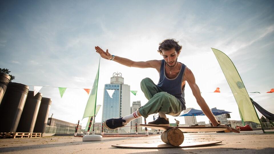 Un jeune acrobate se tient en équilibre sur une bûche de bois surmontée d'une planche.