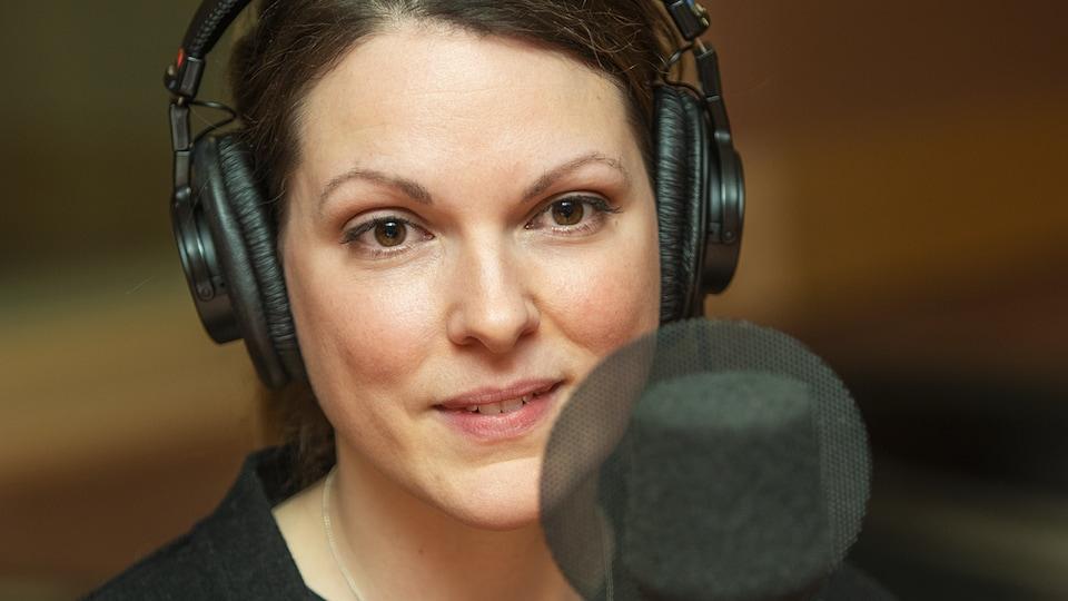 La comédienne derrière un micro dans un studio de radio. Elle porte des écouteurs.