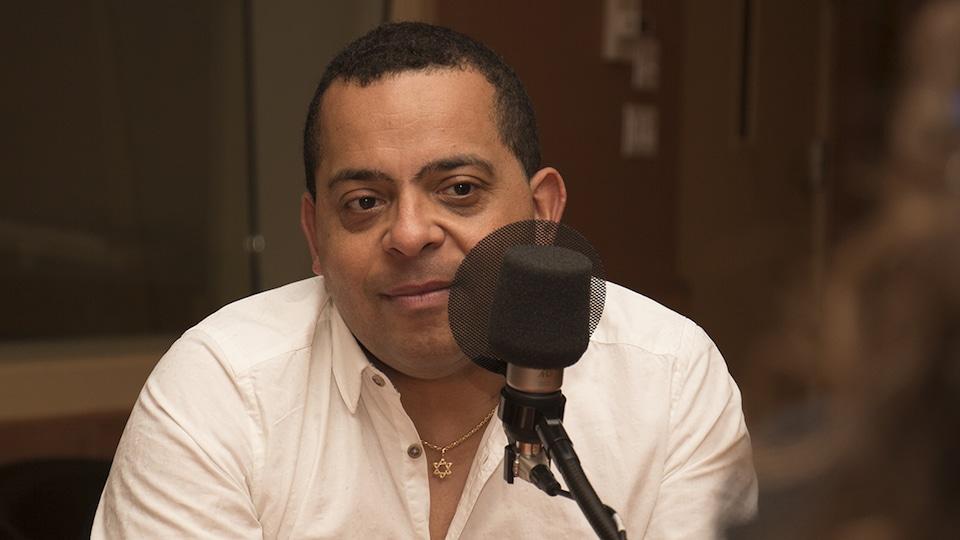 Gregory Charles est assis dans un studio et écoute,  derrière un micro.