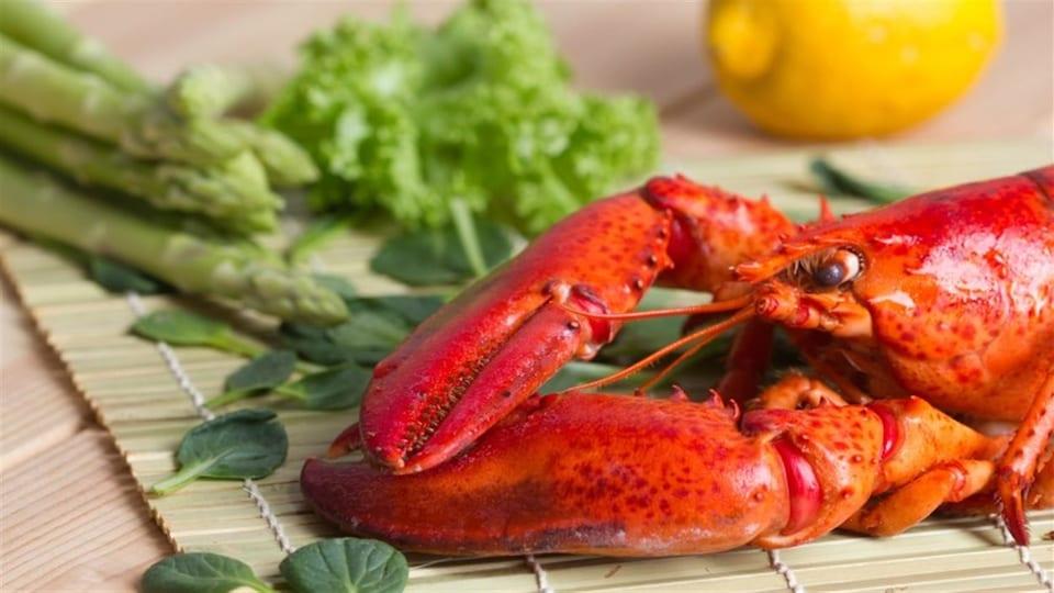 Un homard cuit est posé sur un napperon avec des asperges, des herbes et un citron.